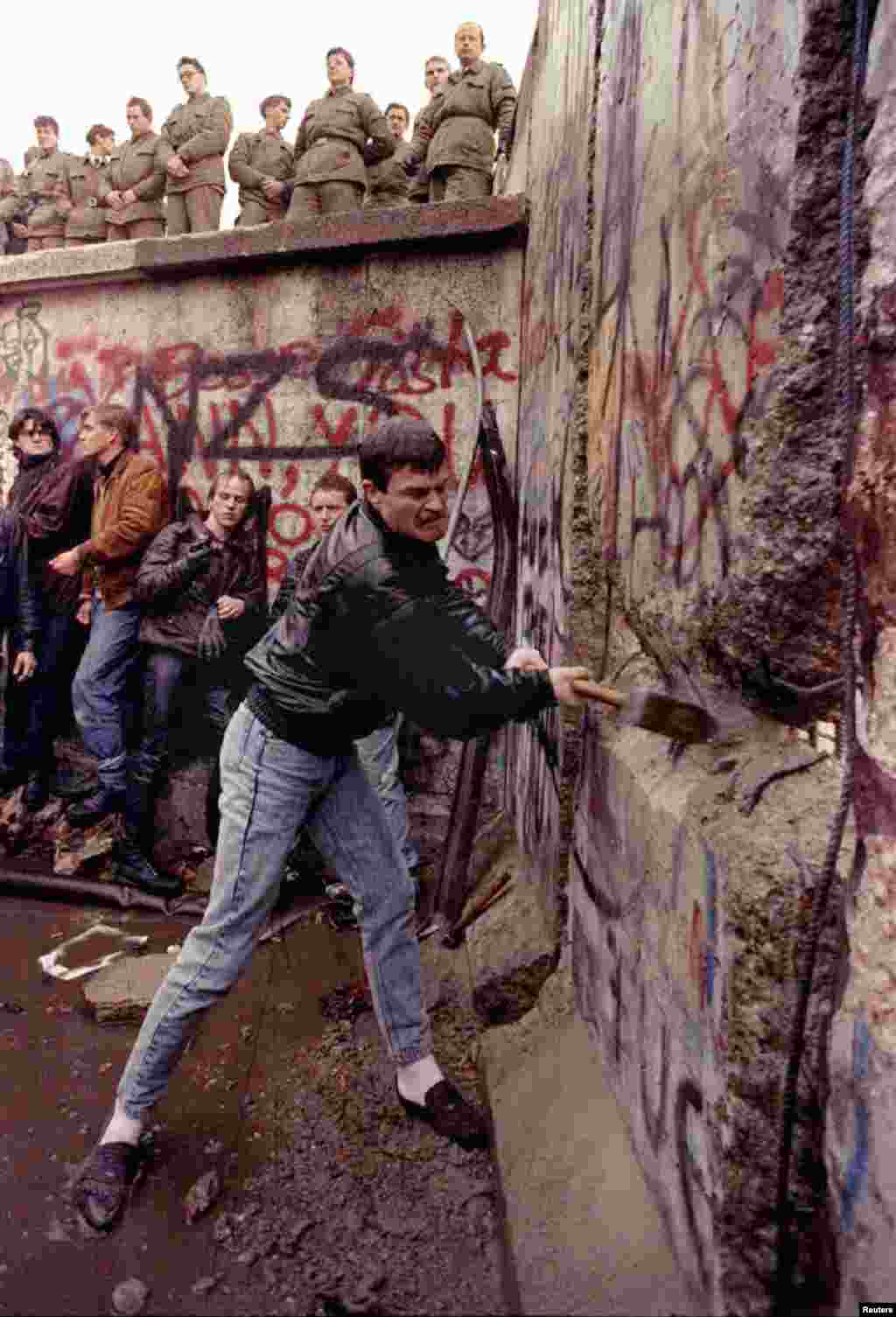 A demonstrator pounds away at the Berlin Wall as East German border guards look on from above at the Brandenburg Gate 11 November 1989.WR - RTRRSTV