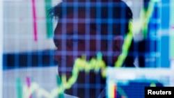 Un corredor de bolsa observa un gráfico en su computadora en la bolsa de valores de Nueva York.