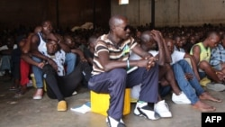 "Men sit in the Gikondo transit center in Kigali, Sept. 24, 2015. Human Rights Watch accused the Rwanda government of rounding up ""undesirables,"" including beggars and prostitutes, and holding them in the center to promote the capital's clean image, a charge denied by the government."
