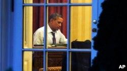 El presidente Barack Obama fotografiado desde la Rosaleda de la Casa Blanca, preparando su discurso de esta noche.