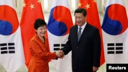 China's President Xi Jinping (R) shakes hands with South Korea's President Park Geun-hye in front of Chinese and South Korean national flags during a meeting at the Great Hall of the People, on the sidelines of the Asia Pacific Economic Cooperation (APEC)