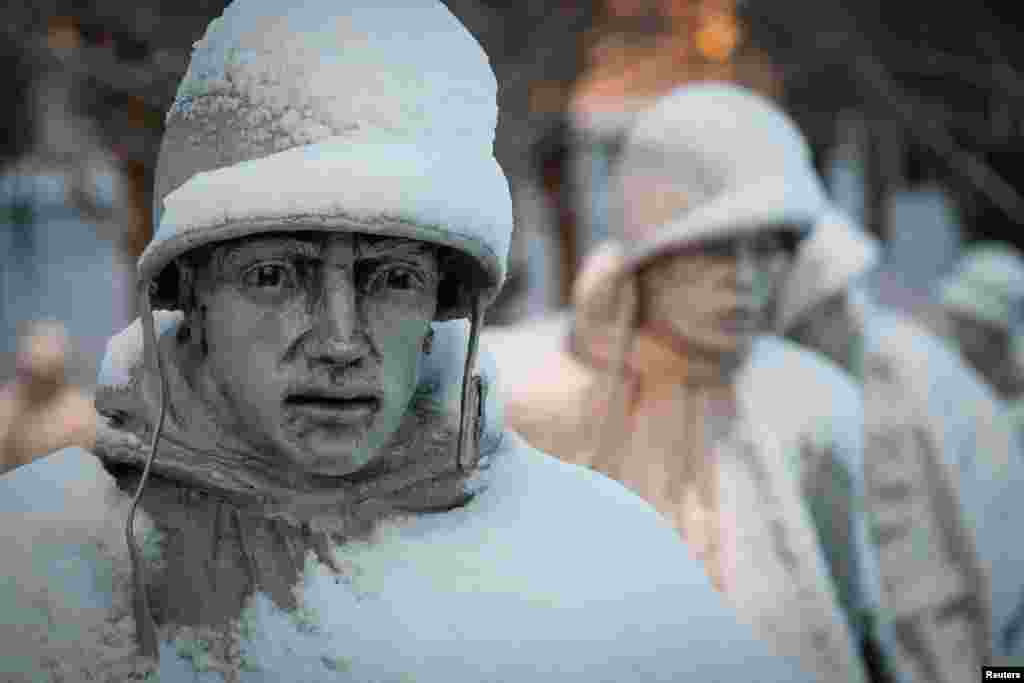A light dusting of snow from an overnight storm covers the statues at the Korean War Memorial in Washington, D.C. early Friday morning. After a storm blew through the region overnight, roads were being cleared and many schools systems were closed.
