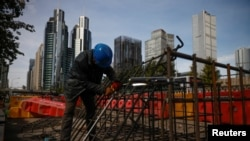 Workers prepares an iron grid for welding at a construction site in the Central Business District, Beijing, China, October 27, 2020.