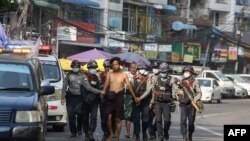 police march with a resident arrested during a crackdown on protesters