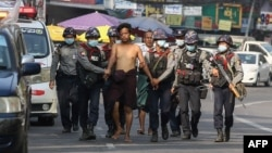 In this file photo taken on February 26, 2021, police march with a resident arrested during a crackdown on protesters holding rallies against the military coup in Yangon. (Photo by AFP)