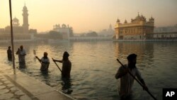 FILE- In this Nov. 17, 2013, file photo, Indian Sikh devotees clean the tank early in the morning at the Golden Temple, on the birth anniversary of Guru Nanak, the first Sikh Guru in Amritsar, India. The chronic air pollution is now threatening the holiest shrine in the Sikh religion, making the once-gleaming walls of the Golden Temple dingy and dull.