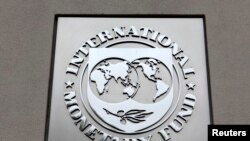 FILE - The International Monetary Fund (IMF) logo is seen at the IMF headquarters building during the 2013 Spring Meeting of the International Monetary Fund and World Bank in Washington.