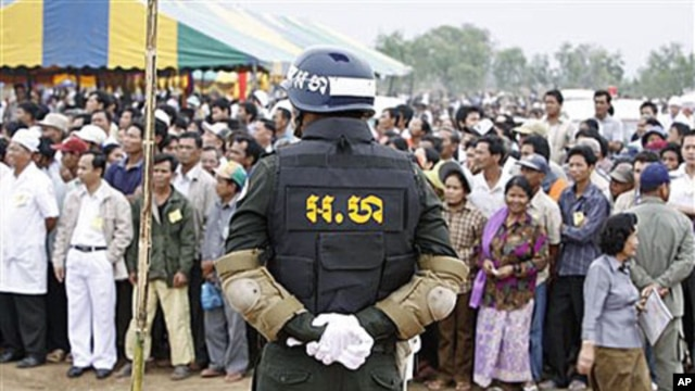 A Cambodian military policeman stands watch during the ground breaking ceremony of a Chinese funded road at Koun Damrey village, Banteay Meanchey province, about 15 kilometers (9 miles) east of Cambodia's border with Thailand, February 15, 2011
