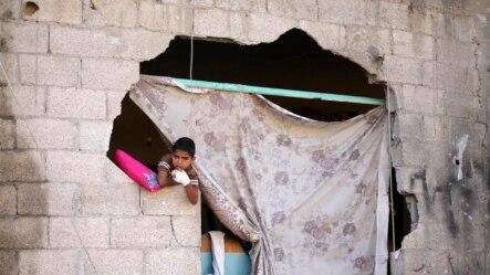 Một cậu bé Palestine ngồi nhìn ra ngoài từ ngôi nhà bị hư hại vì đạn pháo của Israel.