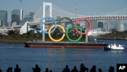 FILE - The Olympic Rings is put back up after they were taken down for repairs ahead of the postponed Tokyo 2020 Olympics in the Odaiba section of Tokyo, Tuesday, Dec. 1, 2020. (AP Photo/Eugene Hoshiko)