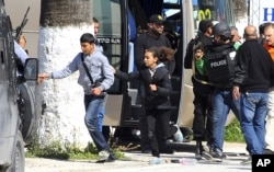 Du khách và trẻ em chạy khỏi hiện trường dưới sự bảo vệ của lực lượng an ninh Tunisia.