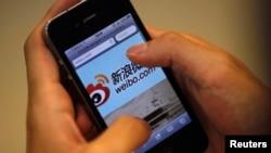 ຜູ້ຊາຍຄົນນຶ່ງ ໃຊ້ iPhone ເຂົ້າໄປເບິ່ງເວັບໄຊທ໌ Sina's Weibo ຂອງຈີນ.