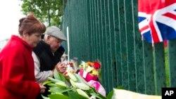 Pasangan Inggris berdoa di luar barak Woolwich, London (24/5), untuk tentara Inggris yang dibunuh sehari sebelumnya di jalan dekat barak. (AP/Bogdan Maran)