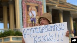 Khek Chan Raksmey of Boueng Kak holds a protest sign as she participates in a rally to ask King Norodom Sihamoni to help release of villagers including her mother in front of Royal Palace in Phnom Penh, Monday, June 11, 2012. The villagers were arrested w