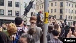Para pengunjuk rasa merobohkan patung Edward Colston dalam unjuk rasa menentang ketidaksetaraan rasial di Bristol, Inggris, 7 Juni 2020. (Foto: tangkapan layar Mohiudin Malik via Reuters)
