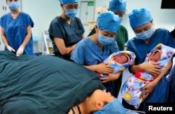 지난 2012년 중국 산시성 시안의 병원에서 간호사들이 쌍둥이 신생아를 산모에게 보여주고 있다.