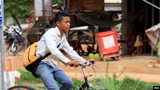 Chheum Sokhoch, 14, rides his bicycle home after school, Siem Reap, Cambodia, July 13, 2017.