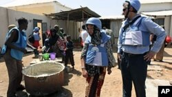 United Nations personnel look on as a worker serves food at a camp in Hodan district in Mogadishu, January 19, 2012