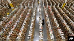 """FILE - An Amazon.com employee stocks products along one of the many miles of aisles at an Amazon.com Fulfillment Center in Phoenix, Arizona, on """"Cyber Monday"""" the busiest online shopping day of the holiday season, December 2013."""
