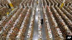 """Pegawai Amazon.com menyusun persediaan barang di salah satu dari banyak lorong penyimpanan di Pusat Persediaan Barang di Phoenix, Arizona, pada hari tersibuk belanja online di musim belanja liburan, """"Cyber Monday,"""" Desember 2013."""