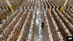يکی از کارمندان شرکت اينترنتی آمازون در شلوغترين روز خريد فصل تعطيلات سرگرم جابجايی محصولات در يکی از مراکز توزيع آمازون در ايالت آريزونا است.