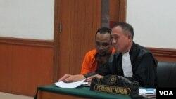 Terdakwa simpatisan ISIS Aprimul Henry alias Mulbin Arifin (kiri) bersama penasihat hukumnya pada sidang lanjutan kasus 7 simpatisan ISIS di Jakarta Barat, Kamis 21/1 (VOA/Fathiyah).
