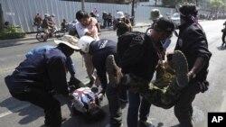 Demonstranti prenose povredjene posle eksplozije tokom antivladinih protesta u Bankoku, 17. januara 2014.