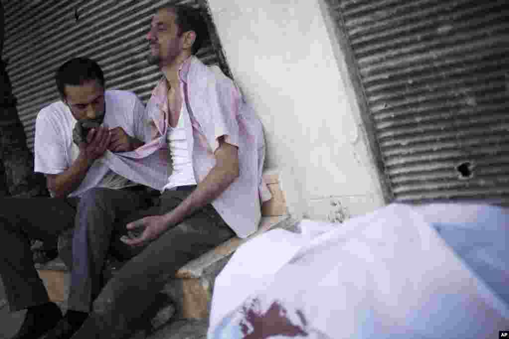 27일 시리아 알레포의 다르엘시파 병원에서 정부군 저격수의 총에 맞아 숨진 시신과, 비통해하는 가족들.