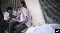 27일 알레포에서 정부군이 쏜 총에 사살된 반군과, 그의 사체 옆에 앉아있는 형제.