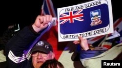 Falkland islanders react after hearing the results of the referendum in Stanley, March 11, 2013. Residents of the Falkland Islands voted almost unanimously to stay under British rule.