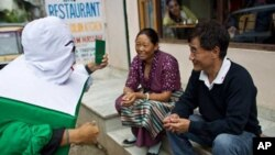 A Tibetan man and woman listen as the 'Green Book Man' explains to them the need to register themselves for the Kalon Tripa and parliamentary elections of 2011 before August 18, 2010, the deadline for registration of voters. Tibetans will go to preliminar