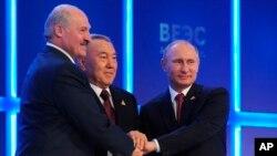 (Từ phải sang) Tổng thống Nga Vladimir Putin, tổng thống Kazahkstan Nursultan Nazarbayev, và tổng thống Belarus Alexander Lukashenko bắt tay sau khi ba nước ký kết thoả thuận thành lập Liên minh Kinh tế Âu Á tại Astana, Kazakhstan, 29/5/2014.