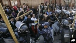Nepalese riot police chase Tibetan exiles with bamboo batons during a rally to mark the anniversary of the failed 1959 uprising against Chinese rule, in Kathmandu, Nepal, Thursday, March 10, 2011. Nepalese police have broken up a protest of more than 1,00
