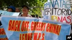 """菲律宾民众2017年3月24日在中国驻菲律宾领事馆前抗议,反对中国在有争议的南中海岛屿上不断进行军事化活动,以及中国船只在""""宾汉隆起""""海域穿梭。"""