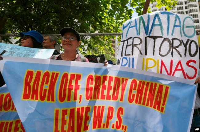 "FILE - Protesters display placards in front of the Chinese Consulate to protest China's alleged continuing ""militarization"" of the disputed islands off the South China Sea including a plan to build a monitoring station on Scarborough Shoal, March 24, 2017."