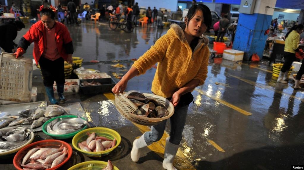 中国福建省泉州市的海鲜市场,一位商贩端着一篮鲜鱼(资料照片,2013年12月9日)