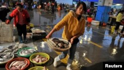 FILE - A vendor carries a basket of fresh fish at a seafood market in Quanzhou, Fujian province, China, Dec. 9, 2013. Joining international sanctions against North Korea, China issued a notice earlier this week stopping imports of iron, lead, coal and seafood from Pyongyang.