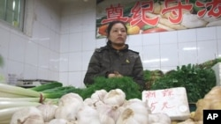 Vegetable seller Wang Yanlin is having trouble moving her garlic supply because customers complain about the higher prices