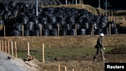 A man walks near waste containing radiated soil, leaves and debris from the decontamination operation at a storage site at Miyakoji area in Tamura, Fukushima prefecture, April 1, 2014.