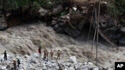 넘치는 강물 때문에 끊어진 다리 주변에 있는 인도 민병대원들