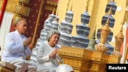 Cambodia's King Norodom Sihamoni (L) and Queen mother Norodom Monineath Sihanouk sit on the royal float as they transport urns with some of the cremains of former late King Norodom Sihanouk from a crematorium to the Royal Palace in Phnom Penh February 7, 2013.