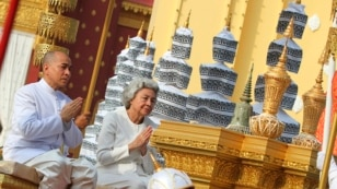 Cambodia's King Norodom Sihamoni (L) and Queen mother Norodom Monineath Sihanouk sit on the royal float as they transport urns with some of the cremains of former late King Norodom Sihanouk from a crematorium to the Royal Palace in Phnom Penh February 7, 2013. Some of Sihanouk's ashes were scattered near the confluence of the four rivers in Phnom Penh on Tuesday, while others were put in three urns, which, according to his wishes, will be placed on the grounds of the royal palace, media reported.
