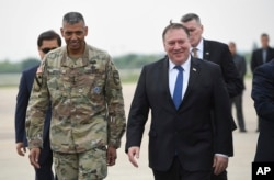 U.S. Secretary of State Mike Pompeo, right, walks with U.S. General Vincent K. Brooks, left, commander of United States Forces Korea, upon his arrival at Osan Air Base in Pyeongtaek, June 13, 2018.