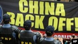 Cảnh sát chống bạo động đứng canh gác trong lúc dân chúng biểu tình bên ngoài Lãnh sự quán Trung Quốc ở thành phố Makati, phía đông thủ đô Manila, Philippines.