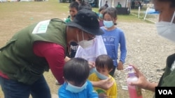 Relawan dari IBU Foundation memasangkan masker wajah pada salah seorang anak di shelter Terintegrasi di Stadion Manakarra, Mamuju, Sulawesi Barat, Minggu, 31 Januari 2021. (Foto: Yoanes Litha/VOA)