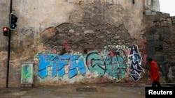 "Seorang pria tunawisma melewati grafiti bertuliskan ""FIFA pulanglah"" di Rio de Janeiro (28/5). (Reuters/Sergio Moraes)"