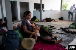 Sandra Aracely Gutierrez, 22, a pregnant Honduran migrant, part of a caravan heading to the U.S., breastfeeds her daughter in downtown San Pedro Tapanatepec, Oaxaca State, Mexico, Oct. 28, 2018.