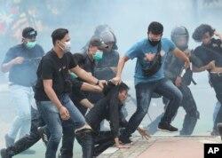 Polisi menahan para demonstran di tengah asap gas air mata dalam aksi yang berakhir rusuh di Jakarta, Kamis (8/10).