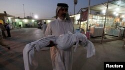 An Iraqi man carries the body of his son, who was killed by a car bomb attack, during a funeral in Najaf, south of Baghdad, Aug. 15, 2013.