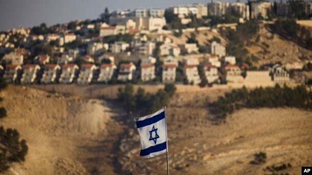 FILE - An Israeli flag is seen near the West Bank Jewish settlement of Maaleh Adumim on the outskirts of Jerusalem in a Sept. 7, 2009, photo. U.S. officials have grown increasingly frustrated with the Israeli government ignoring American official criticism of settlements in the occupied territories.